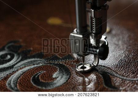 Multilayer embroidery on brown leatherette with embroidery machine - close up with needle down