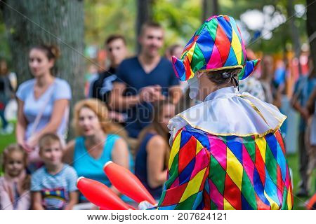 Back view of a street harlequin in colorful costume juggling in the street