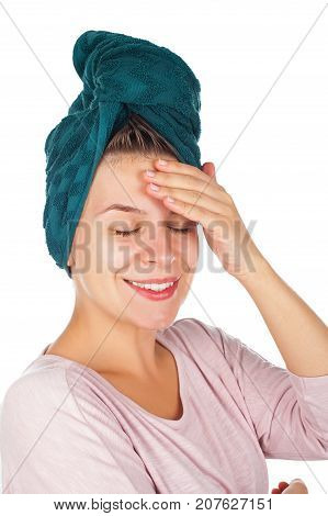 Attractive young woman with bath towel on head applying facial moisturizer