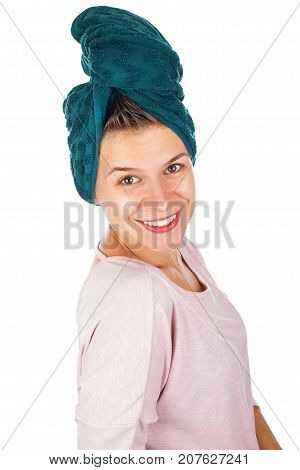 Happy young woman with towel on head applying facial moisturizer after shower