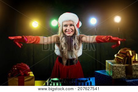 DJ girl in a santa hat is mixed for Christmas.