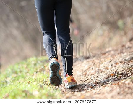 Long Legs Of The Athlete With Black Leggings During The Country