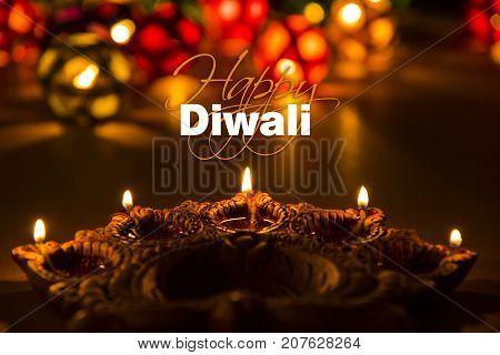 Stock photo of diwali greeting card showing illuminated diya or oil lamp or panti with Happy Diwali text
