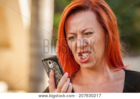 Portrait of a beautiful red hair Caucasian girl screaming on a phone. Hot discussion, quarrel with a boyfriend, spam call, disappointment, upset girl.