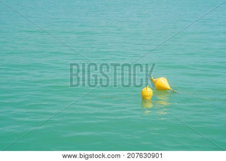 Two Bright Yellow Marker Buoys Floating In Blue Turquoise Lake Water, Balaton, Hungary. Abstract Com