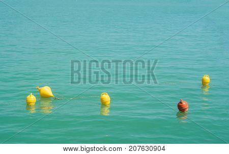 Five Bright Yellow And Orange Marker Buoys Floating In Blue Turquoise Lake Water, Balaton, Hungary.