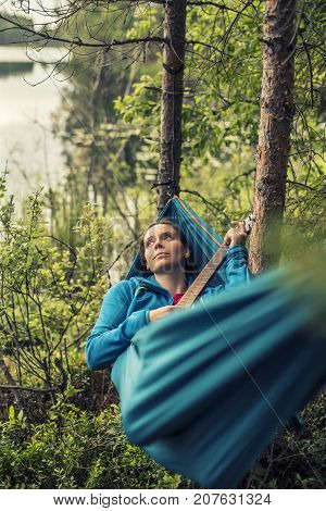 Thoughtful pretty girl lying in a hammock and strumming the guitar melody a summer evening in the woods on a background of lake.