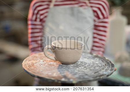 Mid section of female potter holding cup in pottery workshop