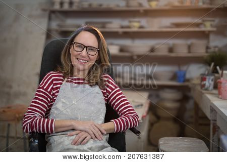 Female potter relaxing on chair in pottery shop