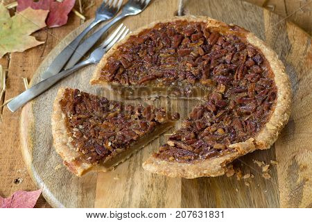 Sliced pecan pie on a wooden plater