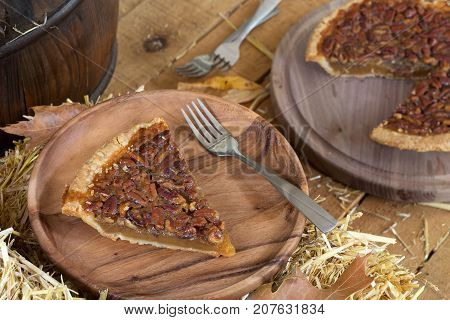 Slice of pecan pie on a wooden plate