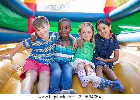 Portrait of friends with arms around sitting on bouncy castle at playground