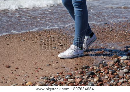 girl dressed in sports shoes walking along the seaside