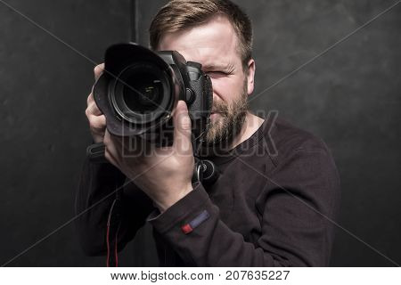 A pretty man - a photographer in a brown sweater shoots in the studio on a DSLR camera which stands on a tripod. Close-up.