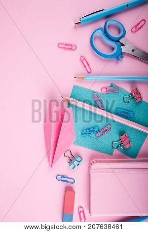 Notebooks, pens, pink paper airplane, scissors, paper clips, rulers of blue and pink colors next to each other on a pink background. Copy space. Close-up of console devices.