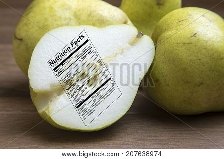 Whole And Sliced Green Pears With Nutrtional Label On Wooden Board