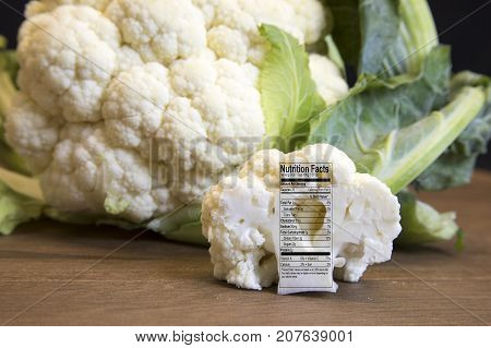 Raw Cauliflower Head And Floret With Nutritional Fact Label On Wooden Board