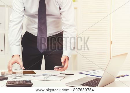Unrecognizable young businessman is looking at his smartphone standing near an office table. Toned image