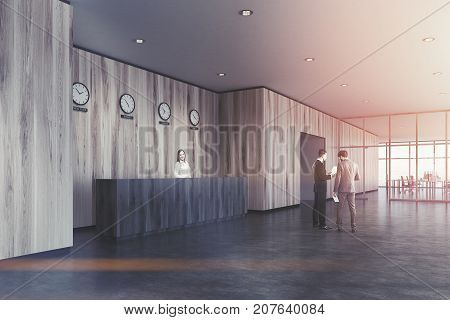 Business people near a wooden reception desk in a modern office with wooden walls and a concrete floor. Clocks showing world time on the wall. Side view. 3d rendering mock up toned image