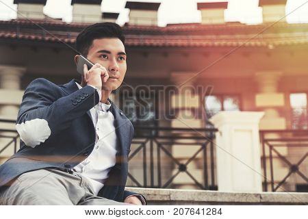 Inspired young Asian businessman is talking on his smartphone while sitting outside near a beautiful building. Toned image