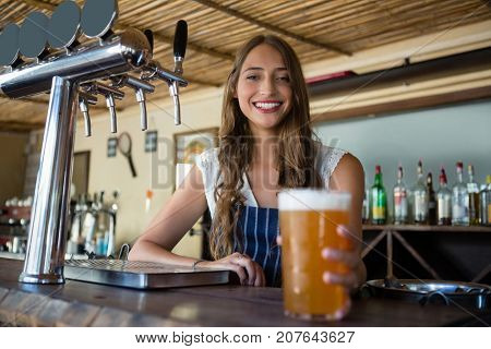 Portrait of happy young barmaid holding beer glass at restaurant