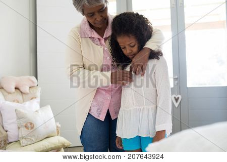 Grandmother dressing up her granddaughter in bedroom at home