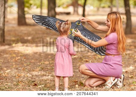 Beautiful little girl trying to fly a kite with a cheerful mother on a blurred autumn park background. Small modern family having fun outdoors.