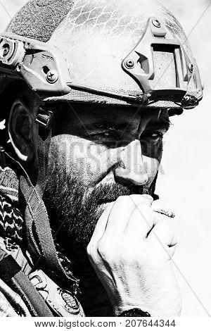 Closeup black and white shot of smoking soldier in the desert among rocks
