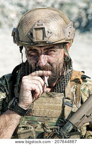 Closeup shot of smoking soldier in the desert among rocks
