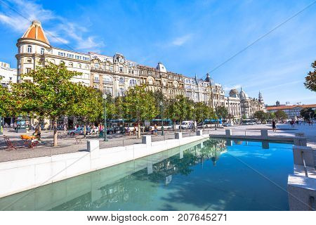 Porto, Portugal - August 11, 2017: monumental historic buildings reflect on artificial reservoir in Avenida dos Aliados, Liberty square, the heart of Oporto city, in a sunny day with blue sky.