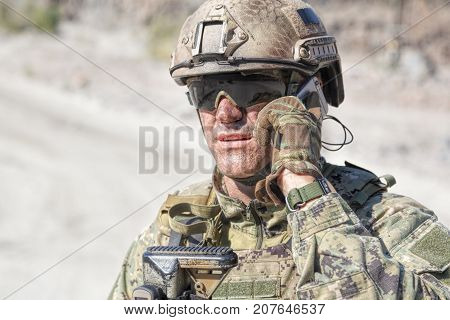 Closeup shot of soldier calliong phone in the desert among rocks