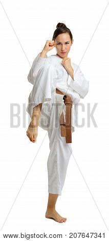 Attractive young girl in karate pose. Isolated on white background. With a brown belt. In full growth.