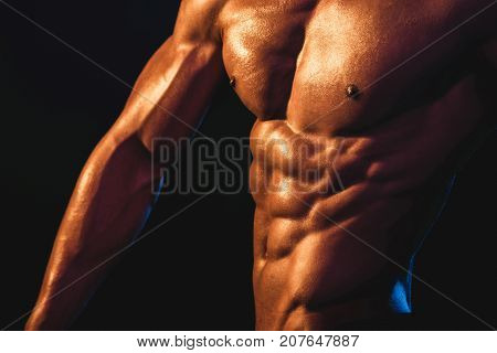 Chest, Arm And Abs Of Young Athlete Close Up. Strong Bodybuilder Shows His Body. Unrecognizable Stro