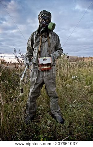 Radiation supervisor in protective clothing and gas mask with geiger counter checks the level of radiation in the radioactive zone