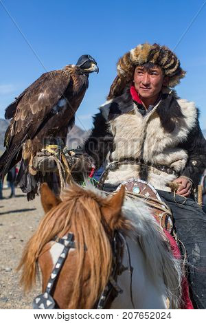 OLGIY, MONGOLIA - SEP 30, 2017: Kazakh Golden Eagle Hunter at traditional clothing, with a golden eagle on his arm during annual national competition with birds of prey