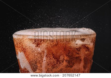 close up ice cola in glass and bubble soda splashing on black background