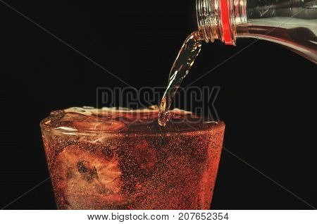 pour cola from the bottle to glass and bubble soda on black background