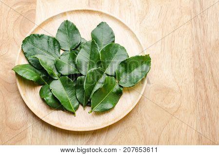 Kaffir Lime (flavorful leaves) on wooden background, food ingredients