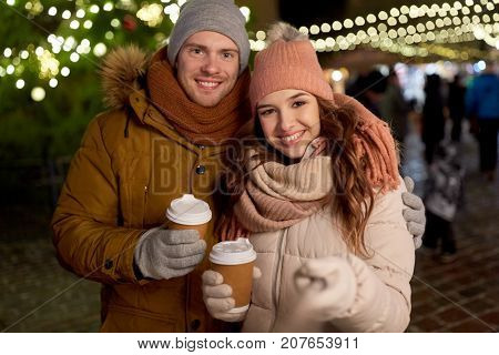 winter holidays, hot drinks and people concept - happy couple with coffee taking selfie in christmas evening