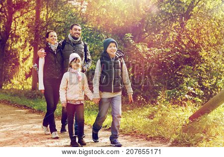 travel, tourism, hike and people concept - happy family walking with backpacks along road in woods