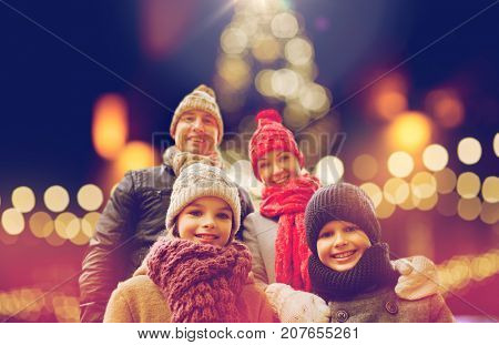 family, holidays and people concept - happy parents with kids outdoors over christmas lights background