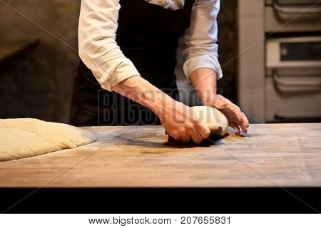 food cooking, baking and people concept - chef or baker making bread and portioning dough with bench cutter at bakery
