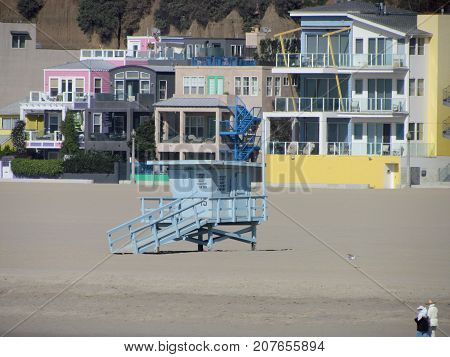 Blue lifeguard tower hut on Santa Monica Beach with colorful houses in background