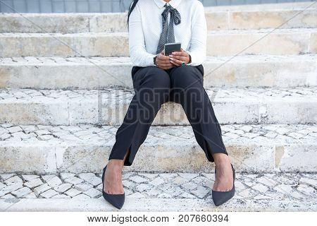 Businesswoman using modern phone outdoors while sitting on stairs alone, Unrecognizable manager in formalwear texting message or checking email on smartphone. Gadget concept