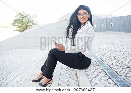 Cheerful businesswoman using mobile phone outdoors and looking at camera. Happy confident female entrepreneur solving urgent issues by means of phone. Manager concept