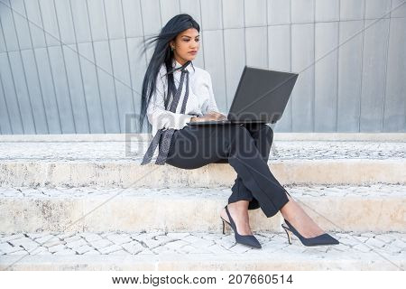 Concentrated businesswoman typing on laptop while composing email outdoors. Mobile female manager examining file using portable computer. Freelance concept