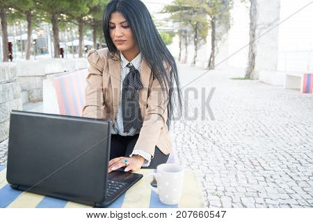 Concentrated businesswoman composing email on laptop while drinking coffee in sidewalk cafe. Busy lady working on portable computer while preparing report out of office. Freelance concept