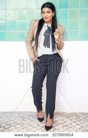 Confident intelligent student girl in formalwear leaning on wall and looking at camera. Serious pretty young Hispanic businesswoman holding eyeglasses. Teacher concept