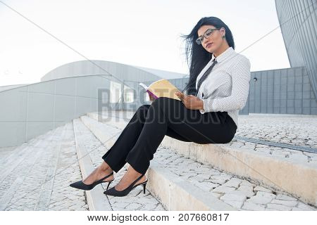 Pensive businesswoman concentrated on book enjoying reading outdoors. Serious beautiful Hispanic lady increasing knowledge about business. Education concept