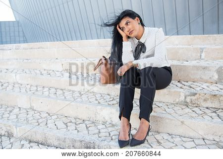 Pensive tired businesswoman waiting for colleague while sitting on stairs outdoors. Displeased young Hispanic female manager looking with sadness away and leaning on hand. Boredom concept